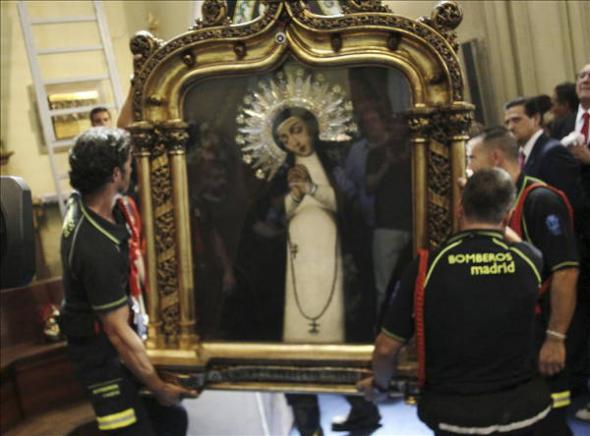 bomberos descolgando la Virgen de la Paloma en Madrid