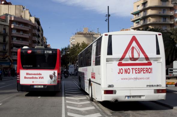 El autobús organizado por asociaciones laicas y ateas, a la derecha, junto a un autobús de línea regular con una publicidad que da la bienvenida al Papa, hoy, en la calle Marina, delante de la Sagr