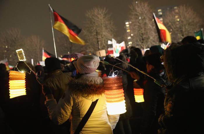 Seguidores del movimiento xenófobo Pegida, acrónimo de 'Europeos patrióticos en contra de la islamización de Occidente', utilizan linternas con los colores de la bandera alemana en su protesta semanal en Dresde.