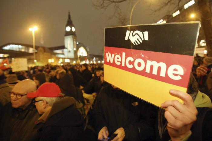 """Uno de los manifestantes a favor de la inmigración muestra un cartel que pone """"Bienvenidos"""", en alusión a las personas de otras razas que llegan a Alemania."""