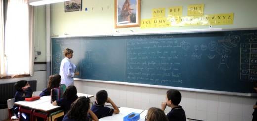 Una profesora da clases a niños de segundo de Primaria en un colegio de Lleida con una imagen de una Virgen en la pared frontal.
