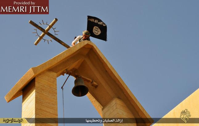 Terroristas del Estado Islámico colocan su bandera en una iglesia cristiana en el norte de Irak.