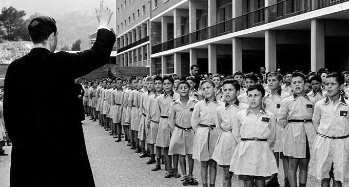 Un sacerdote junto a niños internados en Llars Mundet, en Barcelona.
