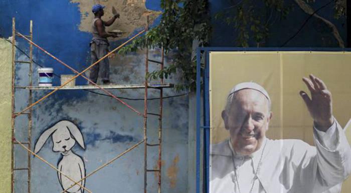 Un obrero repara un muro junto a un cartel del Papa. / REUTERS