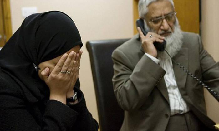 Una mujer en la mezquita de Regent Park, en Londres. A su lado, el juez Suhaib Hasan, uno de los máximos clérigos de la capital británica