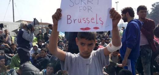 """Un niño refugiado enseña el martes una pancarta con el mensaje """"Lo siento por Bruselas"""" cerca de frontera greco-macedonia.  REUTERS"""