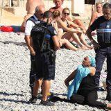 Police controlling on the beach and first person to be fined wearing a burkini on the promenade des anglais beach in Nice on 23/08/2016 LA POLICIA FRANCESA OBLIGA A UNA MUJER ARABE VESTIDA EN LA PLAYA DE NIZA A QUITARSE LA PARTE SUPERIOR DE SU VESTIMENTA. ORIGEN: GTRES